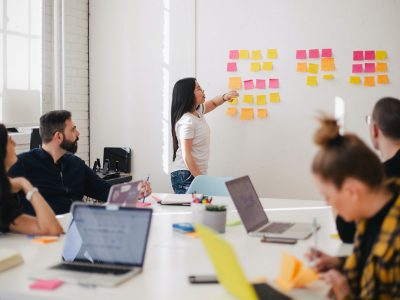 Woman placing sticky notes on wall in conference room