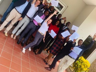 People with certificates in front of buliding